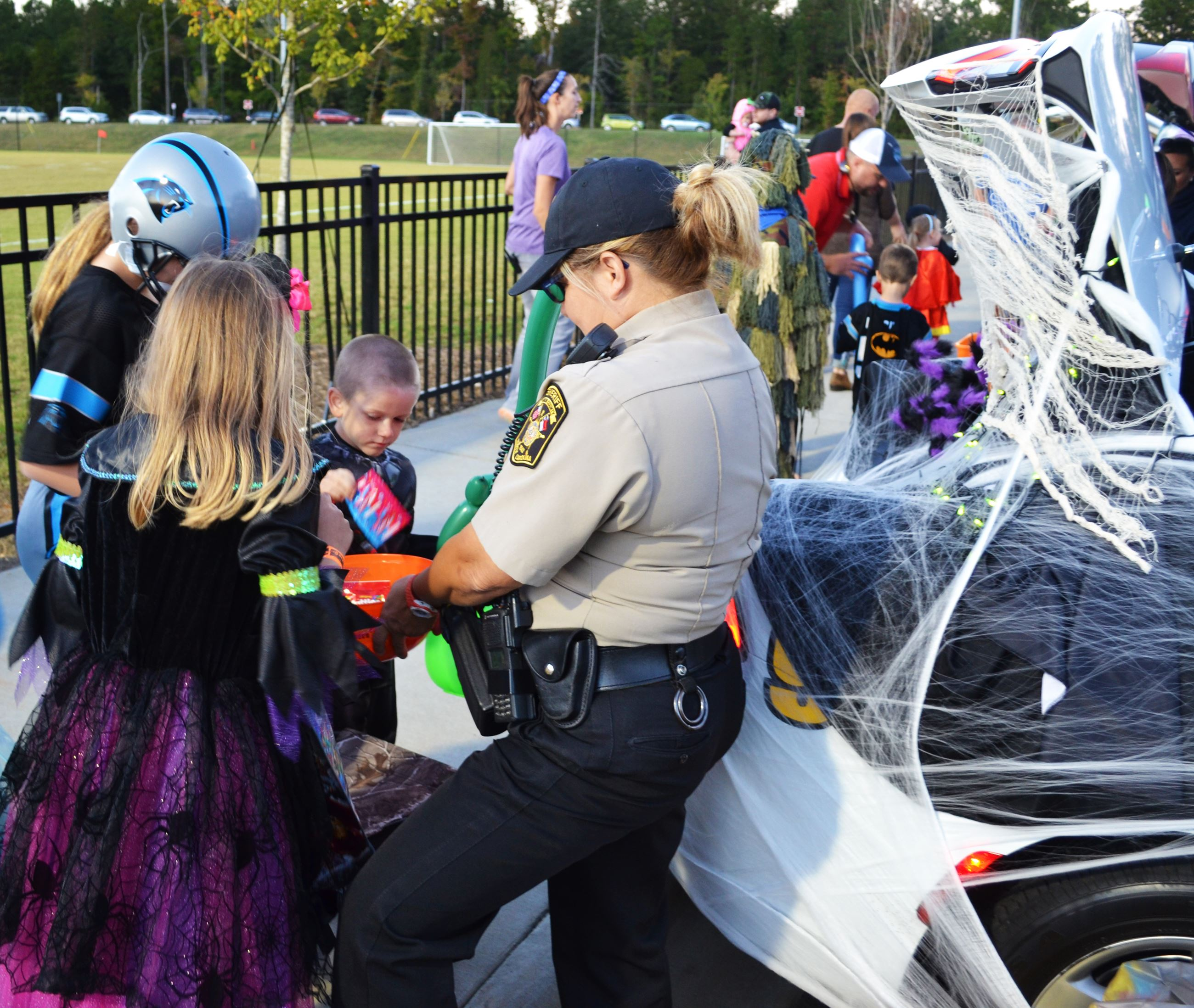 A Sheriff's deputy gives candy to children.
