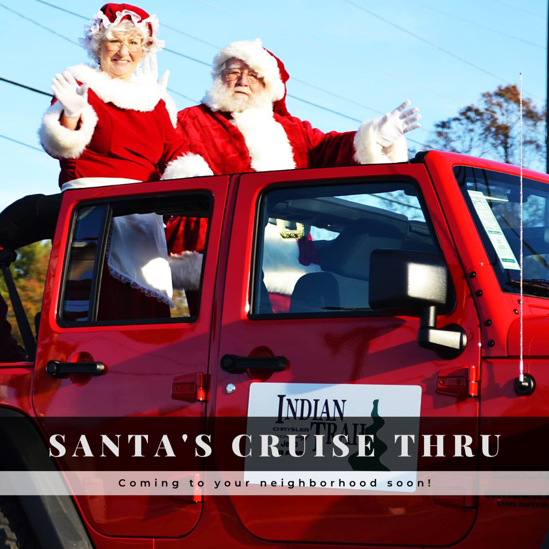 Santa and Mrs. Claus waving while riding in a red Jeep during a Christmas parade.