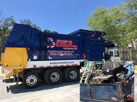 A blue trash truck sits on a gravel drive. A trailer is next to it filled with bulk trash items.